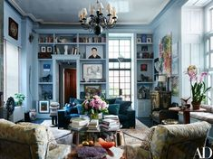 Painted in Benjamin Moore's Whale Gray, Jack Pierson's living room walls and shelves brim with beloved art, books, and objects | archdigest.com