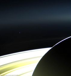 A tiny spot: Planet Earth can been seen as just a miniscule star from this enhanced shot of Saturn taken by the NASA spacecraft Cassini nearly 900million miles away