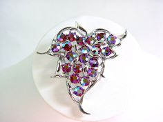 """A Sarah Coventry 'Dazzling Aurora' Borealis leaf brooch. This is a convertible brooch / pendant marked 'Sarah Cov'. The body is filigree silver tone metal and the rhinestones are red with an Aurora Borealis (AB) finish. This brooch was named 'Dazzling Aurora' by the makers. In the shape of a leaf, this AB brooch measures 6 cm X 6 cm (2 3/8"""" X 2 3/8"""") and weighs 22 grams (0.77 oz) This brooch has a sturdy pin with a rollover clasp and a hook that allows attachment to a chain so it can be worn…"""