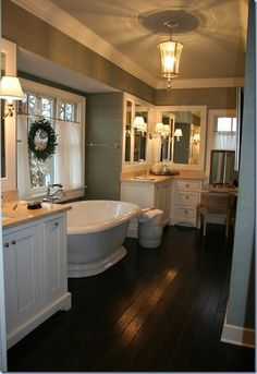 Swing arm light fixtures, white cabinets, wood floor in the bathroom??? risky business.