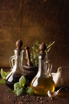 Bottles of olive oil and vinegar, garlic and herbs on a wooden table