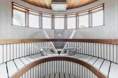 Valkoinen, puolipyöreä sauna merimaisemissa