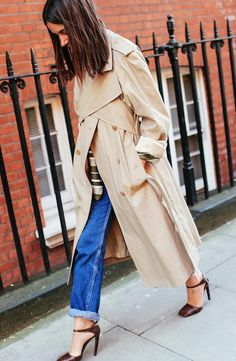 Natasha Goldenberg in a J.W.Anderson top and trench coat paired with cuffed jeans and red heels