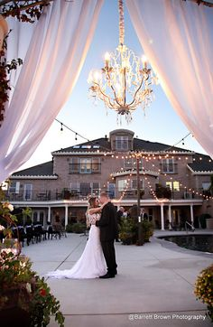 Kayla & Preston alone looking through wedding arch at dusk, party lights on