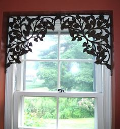 These are shelf brackets, repurposed to frame a window --- what a clever idea. You could do this to define and separate spaces in the same room, too. (Say an entryway and a dining room.)