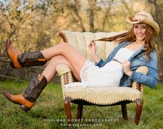 Portrait of Bella Vista high school senior Jessica E. on a vintage chair in a park wearing cowboy hat, jean jacket and boots.