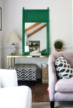 Emerald green frame, gold table, black and white patterned pillow and ottoman, tufted sofa