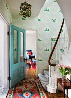 Gorgeous light blue and green flying sparrow birda and cloud wallpaper in the foyer, with a robin's egg blue front door and sweet blue and white striped runner on the spiral staircase. Love this fresh and colorful interior design idea!