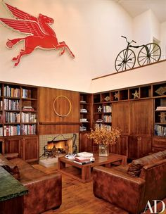 """Wood paneling and cabinets add texture and warmth to the family room, adjacent to the kitchen. """"The more the leather couches are jumped on, the more they'll get a patina,"""" Blake points out. A 1931 Mobil Pegasus is on the wall 