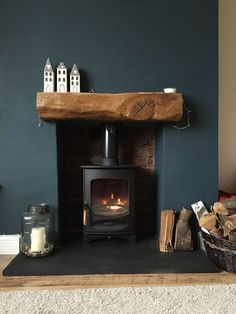 Instant cosiness in a living room. Wood log burner in a dark blue fireplace with wood slab mantle.