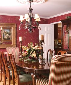 Traditional cherry wood dining set with textured velvet chair seats and dramatic Thybony wallpaper.