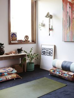 Andrea's yoga and meditation space used for both practice and study. Iconic 'One Eye' poster by Swedish graphic designer Olle Eksell and Rowena Martinich painting. Photo – Eve Wilson. Production – Lucy Feagins / The Design Files.