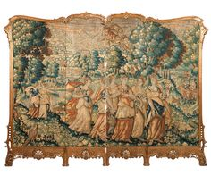 A Large Antique Flemish Tapestry & Carved Giltwood Screen. The tapestry 19th century or earlier, the frame late 19th / early 20th century, the tapestry depicting figures in seventeenth century costume in a verdant landscape, mounted in four panels to the hinged Rococo style frame carved with foliate scrolls, rocaille and pierced palmettes.