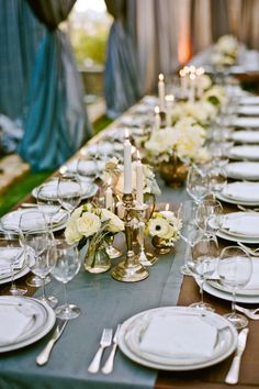 Brass candlesticks and containers look lovely in this backyard wedding tablescape.