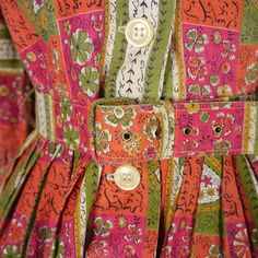 Sweet 50s shirtwaister in a traditional print of florals in red, very dark pink, olive green, black and cream. Fitted bodice with 3/4 sleeves and collared neck. Five white buttons to the chest. Central pleat to the back of the bodice. Fitted waist with a matching belt. Full skirt.