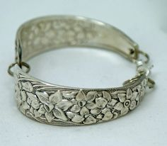 Silverware bracelet. Hm.  Maybe etched & shaped brass or copper plate?  Silver silverware isn't thick on the ground 'round here, but I love the cuffness.