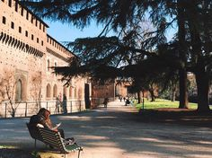 Quintessential Milano: the Castle a clear sunny day and two lovers on a bench in the Sempione Park. by volchitza_