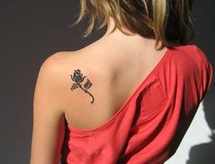 bleiebteste tattoos, frau mit rotem kleid und kleinem rose tattoo