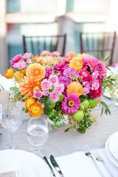 pretty table arrangement with flowers in oranges, purples, pinks with what look like limes as well