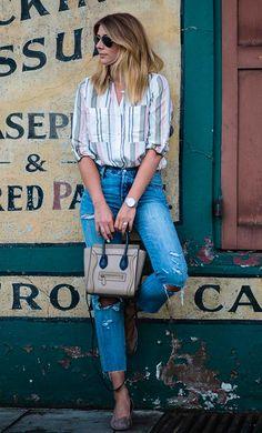 Street style look camisa listrada e calça jeans.