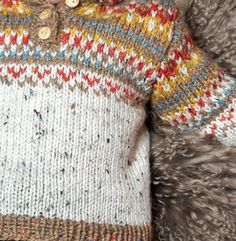 On craque pour ce pull à capuche tweedé et son joli pompon tout coloré, réalisé en 'decoration:underline;color:#6B7785;>Laine Phil randonnées', coloris écru, daim, ambre, dauphin et piment. Modèle N°11 du catalogue N°123 : Automne/Hiver 2015, Spécial Layette.