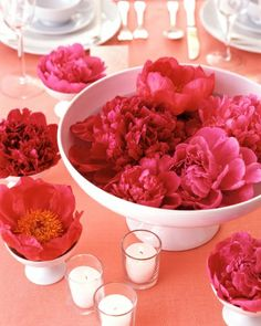 Streamline Centerpieces - Instead of decorating tables with large arrangements, float a few flowers in shallow bowls or glass cylinders filled halfway with water. Here, we floated five or six peony blossoms in a footed bowl, surrounding it with scattered votive candles and satellite peonies in smaller bowls. (I could substitute the big bowl with a pumpkin and use my sunflowers instead of peonies)