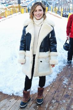 Sophia Bush wears a turtleneck sweater, Coach sheepskin coat, skinny pants, and snow boots