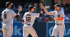 San Francisco Giants' Hunter Pence and Joe Panik high-five while teammate Brandon Belt waits in line after the Giants' 5-3 victory over the San Diego Padres in a baseball game Sunday, July 6, 2014, in San Diego. Pence and Panik scored all five of the Giants' runs and Belt ...