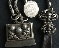 A leather flint pouch with steel striker, suspended by silver chains to a cast silver belt pendant and a Chinese coin toggle dated 34th year of Kuang Hsu (1908). Mongolia. Private collection