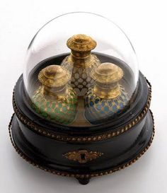 A French Palais Royal Casket, the hinged cover over three coloured opaline glass perfume bottles, c.1840-60, 5in (13.5cm) high.