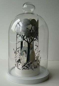 papercut glass domes-These delicate papercuts are by Helen Musselwhite: They wind around inside the glass domes, so you feel as if there is a whole other world within! Her work is spellbinding and wonderfully whimsical!