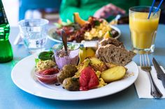 Scandinavian Brunch: scrambled eggs, grilled vegetables, felafel, potatoes, hummus, cheese and fruit; yoghurt with fresh berries and homemade muesli; bread and butter.