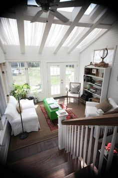 Love this look, with the white walls, the skylights, the dark wood floors, the brick, the white-and-wood railing, and the green coffee table and red rug in the middle of the floor.  It's beautiful.