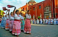 Local women, in colorful embroidered dresses and aprons, celebrate a religious holiday with folk dances. Queretaro, Mexico