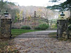 Classic streamlined wrought-iron entry gate with custom scroll finial. Stonework pillars and matching light fixtures. Designed and installed by Tri State Gate in Westchester County, New York. Aluminum Driveway Gates, Electric Driveway Gates, Wrought Iron Driveway Gates, Driveway Entrance, Metal Gates, Front Gates, Entrance Gates, Iron Gates For Sale, Wood Fence Installation