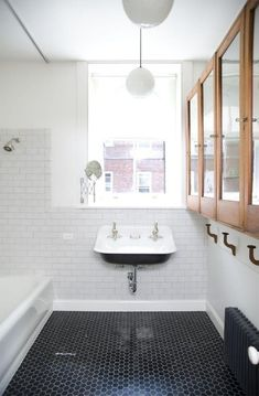 Bathroom white subway tile and black penny tile