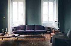 Sanfte Blaugrüntöne und das Violett des Sofas  verbinden sich harmonisch mit warmem Holz
