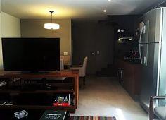 Sala de estar integrada com sala de jantar e cozinha. Atmosfera sóbria e masculina com tons de cinza. Móvel da tv em madeira escura divide sala de estar e jantar. Piso em porcelanato cinza com acabamento natural