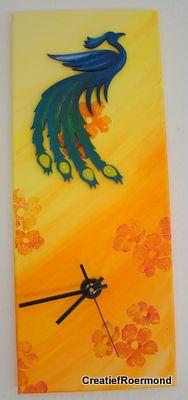 Canvas eerst in kleur gesponsd, daarna gestempeld. Paradijsvogel is een kant en klaar mdf-figuur. Een gaatje voor het uurwerk en je hebt een originele klok. Tip: Laat het uurwerk aan de achterkant steunen op het hout van het canvas.