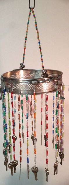 Silver plated casserole serving ring repurposed into a wind chime.  Numerous needs in variety of colored beads. Finished off with several keys which tinkle together in the wind.