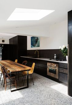 white terrazzo floor contrasts with black kitchen cabinets and stained wood furn. - white terrazzo floor contrasts with black kitchen cabinets and stained wood furniture - Kitchen 2016, Kitchen Dining, Kitchen Decor, Brass Kitchen, Kitchen Black, Terrazzo Flooring, Kitchen Flooring, Concrete Floors, Grey Kitchens