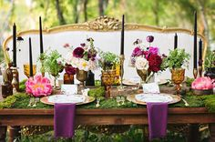 Forest Feast ~ We are totally jonesing for this mix of amber glassware and deep purple peonies, coupled with moss placemats and prime couch seating. Whoa, this table just transported us to an enchanted forest. Via Julie Wilhite.