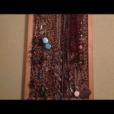 Organized thanks to an idea I saw on Pinterest! My cheap necklaces are no longer tangled, hanging on my bedroom door knob! I covered an old cork board with leopard print duct tape I bought at Michael's craft store for $5. I hung necklaces, bracelets, and earrings with black tacks. Viola, organized!