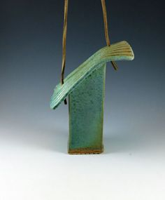 A unique ceramic birdhouse. Handmade garden art pottery by Botanic2Ceramic.    The roof is set at a jaunty angle with just the right bit of attitude. It is glazed in weathered bronze which is a natural green verdigris on copper color. Made of high fired white stoneware, it is extruded to get the rectangle shape, the a slab is rolled and carved to make the roof and the base. There is a small hole in the bottom for drainage. It can be hung by its heavy duty leather cord.    This birdhouse has…