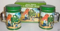 "John Deere Salt & Pepper Shakers by John Deere. $8.99. Licensed John Deere Salt & Pepper Shakers.. John Deere 1934-1952 Model A Tractor.. Has the big ""S"" and ""P"" spelled out with holes on top for free flowing salt and pepper.. Tin cup style with removeable cap for filling.. Fabulous graphic of a Model A John Deere tractor in the corn field with a little girl bringing her father lunch in a picnic basket.  A true to life American scene in the day."