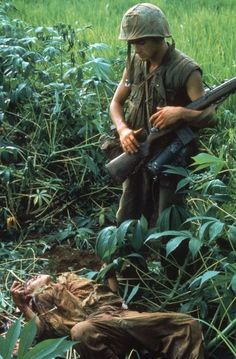 Image not published in original story in LIFE.  An American Marine looks at the body of a North Vietnamese  killed during Operation Prairie near the DMZ during the Vietnam War, October 1966.