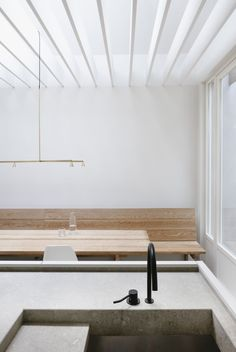 Renovation House V is a minimal home located in Antwerp, Belgium, designed by Hans Verstuyft Architecten. The space is characterized by the use of raw materials, mostly concrete, mixed with the warmth of natural wood. An array of planks are used for the ceiling within the kitchen to create depth, and filter natural light from above. A custom-built wooden bench maximizes the wall space, matching the grain from the dining table.