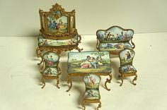 SEVEN-PIECE VIENNESE ENAMELED MINIATURE SALON SUITE comprising of a settee, four chairs, a salon table, and bureau plat Condition: with crazing to enamel the largest: 4 1/2 inches high