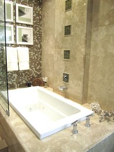 Travertine and Glass Bathtub with waterfall faucet.
