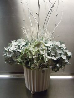 a decoration with hydrangea heads, everything sprayed whitish and smallest amount of frosting sprinkled over